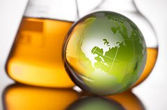 green glass globe in front of labe beakers with orange liquid
