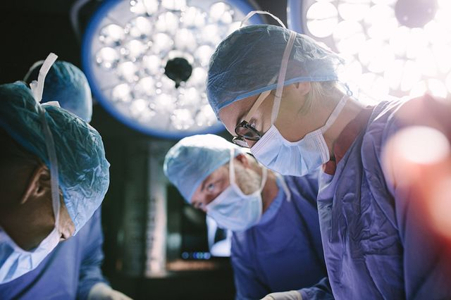 Concentrated female surgeon performing surgery with her team in hospital operating room.