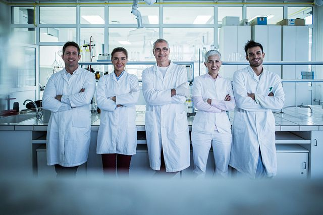 Group of smiling chemists standing in a laboratory with their arms crossed and looking at the camera.