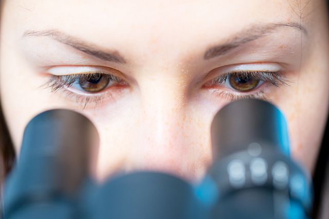 scientist woman looking in microscope
