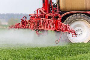 Red tractor fertilizing a field.