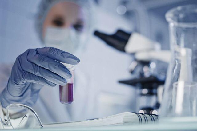 Scientist performing virus lab tests wearing protective workwear.