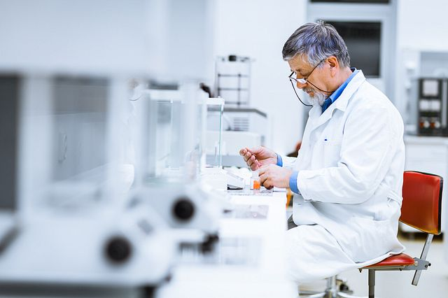 male technician engaged in biologics testing activities in a laboratory setting