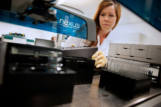 gowned and gloved technician using the nexus machine