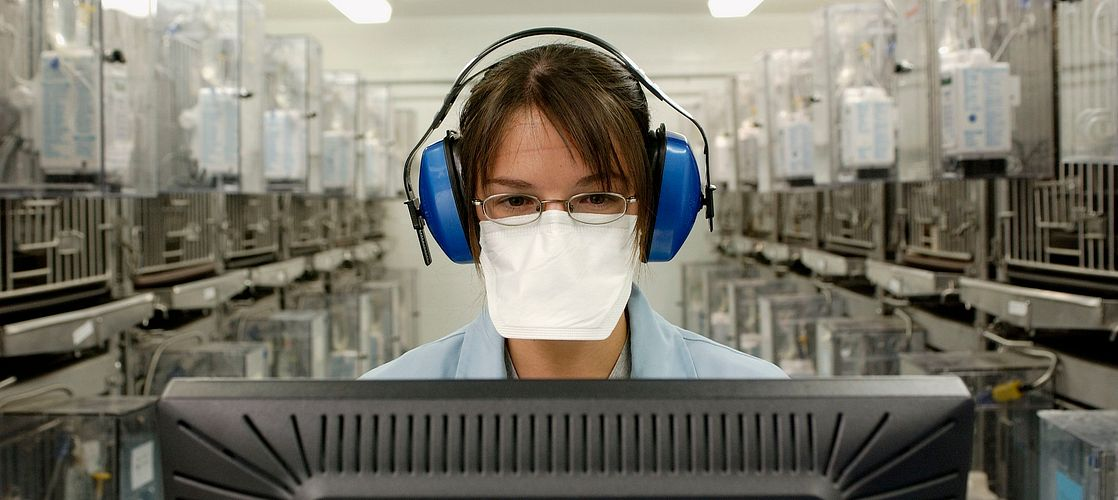 Safety Assessment technician at computer in Toxicology animal room.