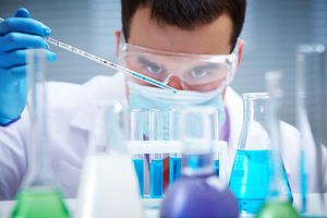 Investigator checking test tubes, Man wears protective goggles, scientist pipetting samples