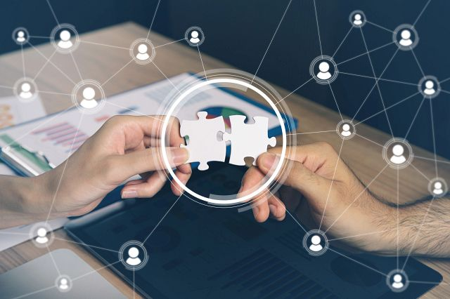 Concept image of people holding two puzzle pieces together illustrating collaboration.