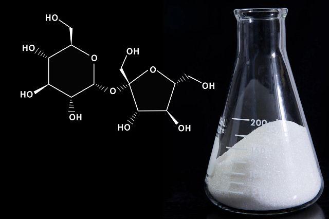Food science - sugar in Erlenmeyer flask with molecular formula of sucrose on a black background.